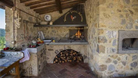 Buitenkeuken met houtoven en barbecue.