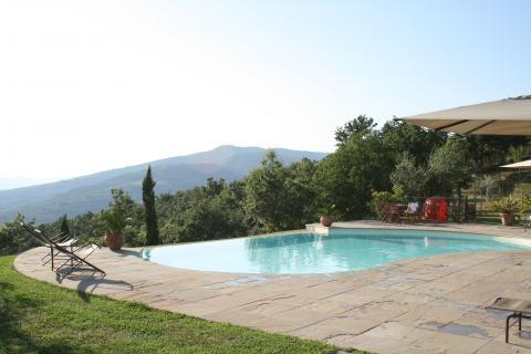 Uitzicht op het zwembad en de groene Toscaanse heuvels.